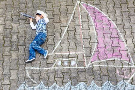 kids having fun: Cute little boy sailing on ship or boat picture drawing with chalk. Creative leisure for children outdoors in summer