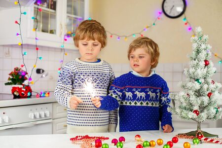 pullovers: Two little kids, best friends in winter pullovers holding burning sparkler on Christmas Eve. Safe fireworks for kids concept. Happy sibling  boys outdoors.