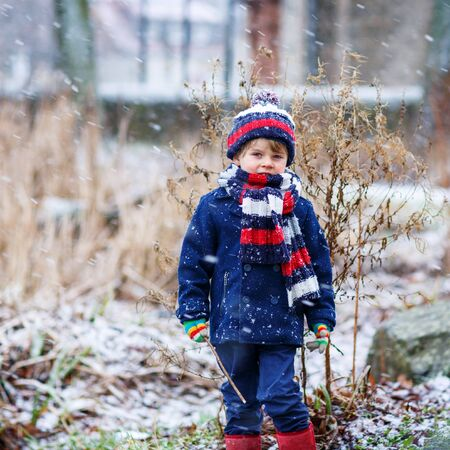 outoors: Winter portrait of kid boy in colorful winter clothes, outdoors during snowfall. Active outoors leisure with children in winter on cold snowy days