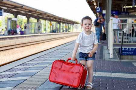 holidaymaker: Beautiful little girl walking with big red suitcase on a railway station. Kid waiting for train and happy about a journey. People, travel, lifestyle concept