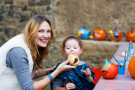 german sausage: Young beautiful mother feeding her little daughter, adorable kid girl with hot dog or German sausage on thanksgiving or halloween pumpkin festival, outdoors. Family enjoy warm autumn day.
