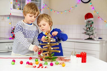 pullovers: Two adorable kidsdecorating selfmade Christmas tree. Happy friends, children in xmas pullovers. Kitchen decorated for Christmas. Family, holiday, kids lifestyle concept.
