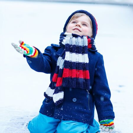 having fun in the snow: Lovely little funny kid in colorful winter clothes having fun with snow, outdoors during snowfall. Active outoors leisure with children in winter. Kid with warm hat, hand gloves and scarf with stripes. Happiness about snow. Stock Photo