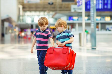 pilot: Two tired little sibling kids boys at the airport, traveling together. Angry family, twins children waiting. Canceled flight due to pilot strike.