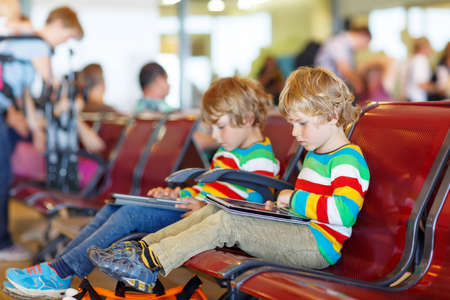 pilot: Two tired little sibling kids boys at the airport, traveling together. Upset children waiting and playing with tablet pc. Canceled flight due to pilot strike.