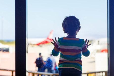gente aeropuerto: Lindo niño pequeño niño cansado en el aeropuerto, viajando. Niño trastornado esperando cerca de la ventana y mirando el avión. Cancelado el vuelo debido a huelga de pilotos.