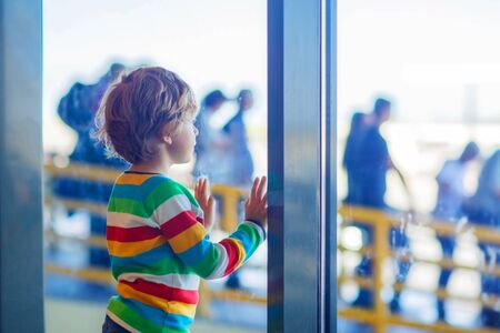 airline pilot: Cute little tired kid boy at the airport, traveling. Upset child waiting near window and looking at plane. Canceled flight due to pilot strike.