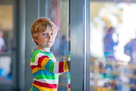 pilot: Cute little tired kid boy at the airport, traveling. Upset child waiting near window and looking at plane. Canceled flight due to pilot strike.
