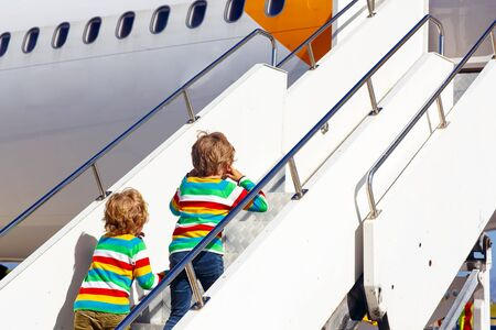 sibling: Two tired little sibling kids boys at the airport, traveling together. Upset children climbing stairs on plane. Canceled flight due to pilot strike. Stock Photo