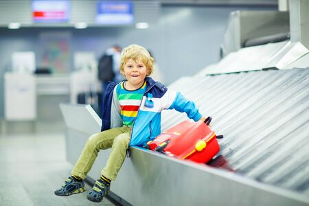 Adorable little tired kid boy at the airport, traveling. Upset child waiting with kids suitcase on baggage carousel. Canceled flight due to pilot strike.
