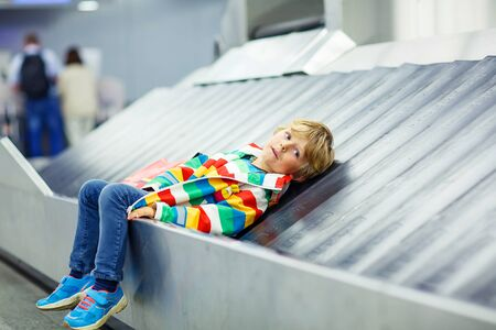 airline pilot: Adoralbe little tired kid boy at the airport, traveling. Upset child waiting with kids suitcase on baggage carousel. Canceled flight due to pilot strike.