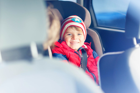 hapy: Portrait of hapy little kid boy sitting in car. Child in safety car seat with belt. Safe travel with kids and traffic laws concept.