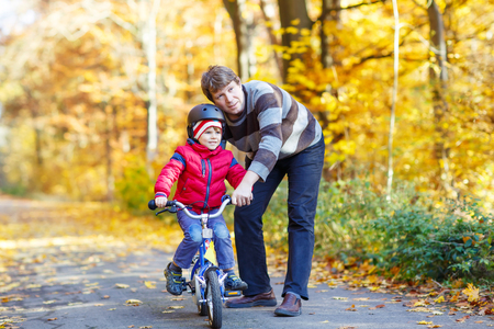 father: Young man and his little son, kid boy in autumn forest with a bicycle. Father teaching biking. Active family leisure. Child with helmet. Safety, sports, leisure with kids concept.