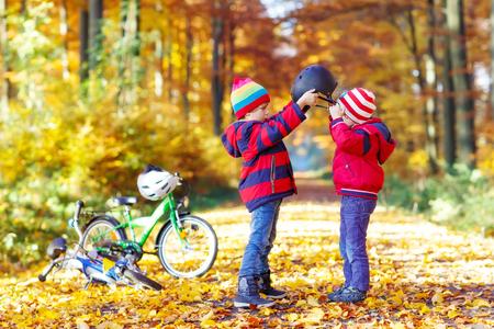 Dvě malé děti kluci, nejlepší kamarádi v podzimním lese. Starší bratr pomůže mladšímu dítěti, aby položil přilbu. Šťastné sourozenci s jízdními koly. Reklamní fotografie