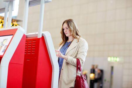 piloto: Mujer joven cansada en el aeropuerto internacional de registrarnos en el terminal electr�nico de espera de su vuelo. Malestar de pasajeros. Cancelado el vuelo debido a huelga de pilotos. Foto de archivo