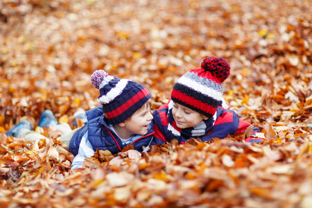 kiddies: Two little twin boys lying in autumn leaves in colorful clothing. Happy siblings kids having fun in autumn forest or park on warm fall day. With hats and scarfs