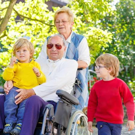 silla de ruedas: Niños entre hermanos, su abuela y abuelo en silla de ruedas en el jardín de verano. Familia feliz pasar tiempo juntos. Foto de archivo