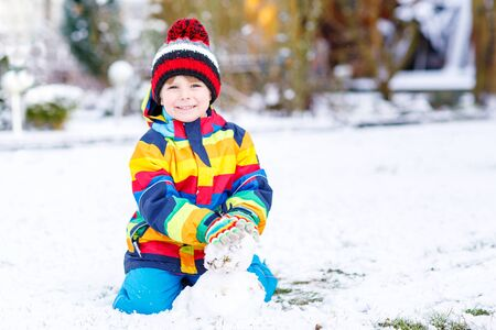 having fun in the snow: Beautiful kid boy in colorful clothes making a snowman, playing and having fun with snow, outdoors  on cold day. Active outoors leisure with children in winter.