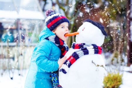 having fun in the snow: Cute little kid boy making a snowman and eating carrot. child playing and having fun with snow on cold day. Active outdoors leisure with kids in winter. Stock Photo