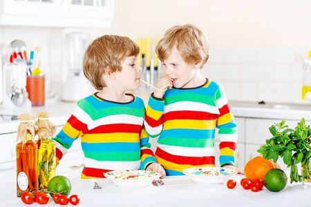 niños comiendo: Dos niños divertidos que comen comida con pasta y verduras frescas en la cocina doméstica, en el interior. Hijos de hermanos con camisas de colores.