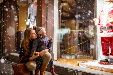christmas market: Little toddler girl with mother on Christmas market. Funny happy kid making window shopping with  Santa Claus. holidays, christmas, childhood and people concept. family during winter snowfall