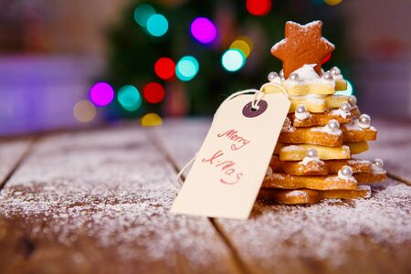 grunge border: Home made baked Christmas gingerbread cookie tree as a gift for family and friends on wooden background. With colorful lights from Christmas tree on background. With icing sugar as snow.