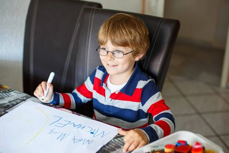 preschool: Portrait of cute happy preschool kid boy with glasses at home making homework. Little child writing mama with colorful pencils, indoors. School, education concept