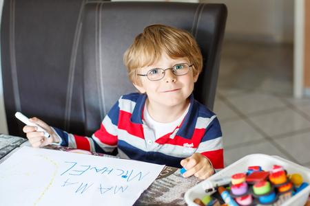 preescolar: Retrato de lindo niño feliz niño preescolar con gafas en la toma de la casa los deberes. Pequeño niño escribiendo mama con lápices de colores, en el interior. Escuela, concepto de la educación Foto de archivo