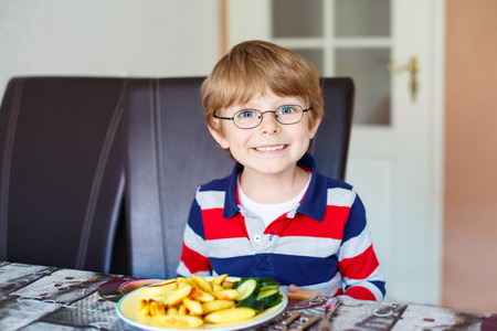 having fun: Happy adorable kid boy with glasses eating healthy food in kindergarten or at home. Fresh vegetables as snack for children.