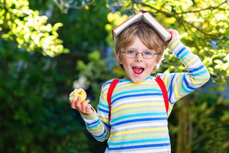 Glückliches kleines Kind Junge mit Brille, Bücher, Apfel und Rucksack an seinem ersten Tag in der Schule oder Kindergarten. Kind im Freien an warmen sonnigen Tag, zurück zur Schule Konzept