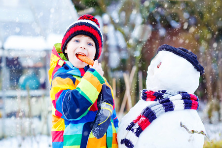 Beautiful little kid boy making a snowman and eating carrot. child playing and having fun with snow on cold day. Active outdoors leisure with kids in winter. Stock Photo