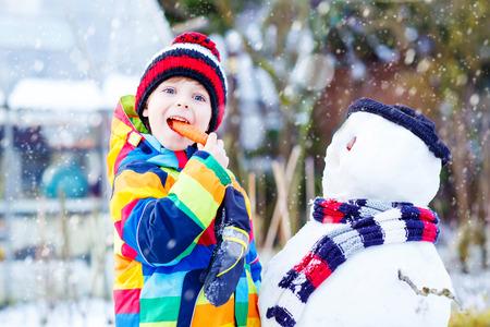 bonhomme de neige: Belle gamin gar�on faisant un bonhomme de neige et de manger la carotte. enfant jouant et avoir du plaisir avec de la neige le jour froid. ext�rieur loisir actif avec des enfants en hiver. Banque d'images