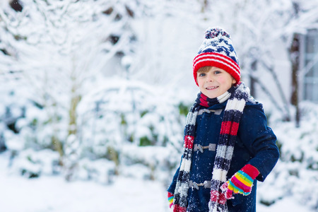 winter clothes: Winter portrait of kid boy in colorful clothes, outdoors during snowfall. Active outoors leisure with children in winter on cold snowy days. Happy child having fun with snow
