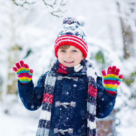 having fun in the snow: Winter portrait of kid boy in colorful clothes, outdoors during snowfall. Active outoors leisure with children in winter on cold snowy days. Happy child having fun with snow