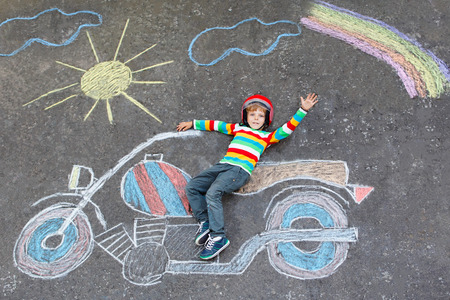 chalks: Happy little kid boy  in helmet having fun with motorcycle picture drawing with colorful chalks. Children, lifestyle, fun concept. child dreaming of future and profession.