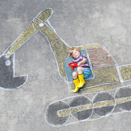 alone boy: Happy funny little kid boy having fun with excavator picture drawing with colorful chalk. Creative leisure for children outdoors in summer.