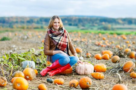 field crop: Beautiful young woman in red rain boots working on pumpkin farm or patch. Girl having fun with farming. Thanksgiving, harvest or halloween concept