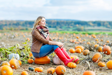 thanksgiving adult: Beautiful young woman in red rain boots working on pumpkin farm or patch. Girl having fun with farming. Thanksgiving, harvest or halloween concept