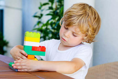 baby boys: Adorable little blond child playing with lots of colorful plastic blocks indoor. Active kid boy having fun with building and creating.