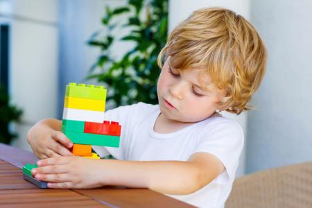 Schattig klein blond kind dat met veel kleurrijke plastic blokken indoor. Active kid jongen die pret met de bouw en het creëren.