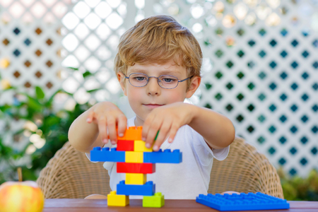 Adorable little blond kid with glasses playing with lots of colorful plastic blocks indoor. Active child having fun with building and creating. Creative Leisure for children. Banque d'images