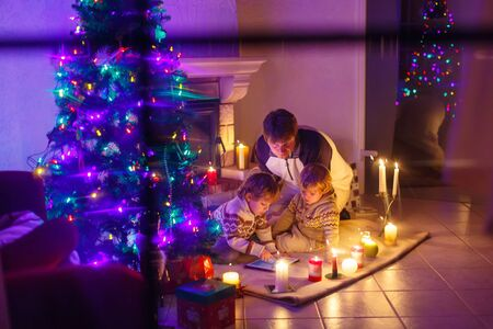 baby open present: Young father and his two little children sitting by a fireplace at home on Christmas time. Kids boys playing with tablet. Through window from outdoors