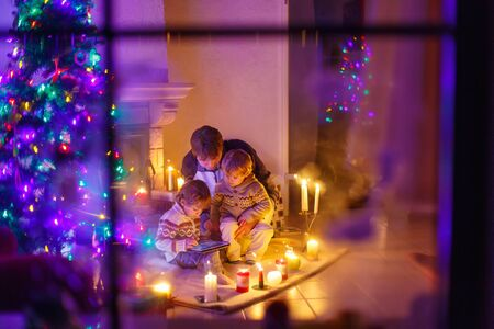 Young dad and his two little sons sitting by a fireplace at home on Christmas time. Kids boys playing with tablet. Through window from outdoors