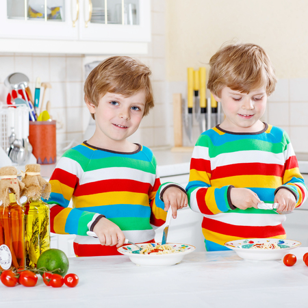 guy portrait: Two funny kid boys of 4 years eating pasta and fresh vegetables in domestic kitchen, indoors. Sibling children in colorful shirts.