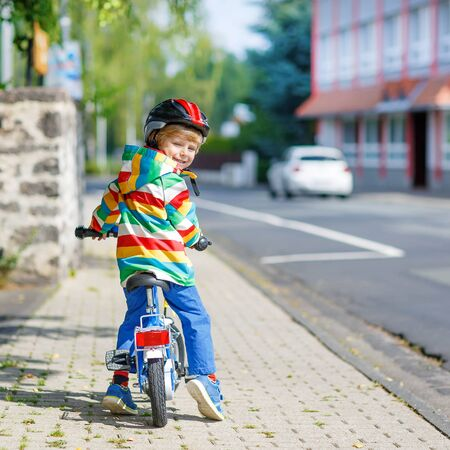 first day: Adorable kid boy in red safety helmet and colorful raincoat riding his first bike on summer day. Active leisure for children outdoors. Stock Photo