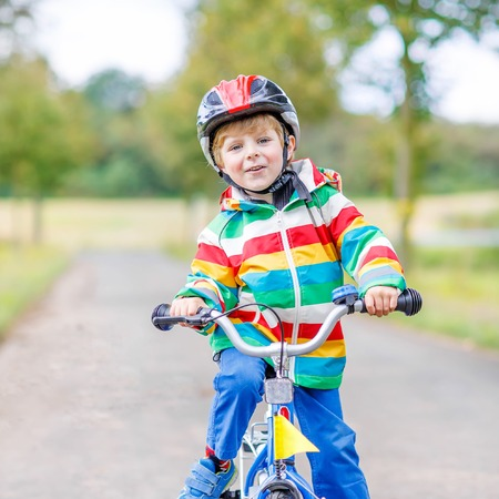 preschool boys: Cute active little boy riding on bike on warm summer day. Countryside. Child in helmet. Active leisure and sports for kids.