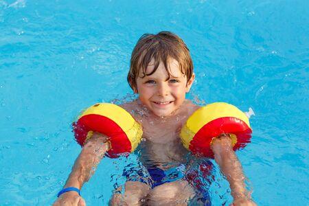 persona alegre: El niño pequeño lindo que se divierte en una piscina. Niño activo feliz que lleva swimmies seguras. La familia, las vacaciones, el concepto de verano. Foto de archivo