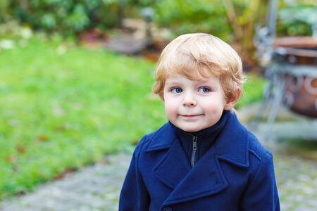 warm clothing: Happy little blond toddler boy walking on cold day in blue coat. Funny kid wearing wam clothes on cold autumn or spring day. Carefree childhood. Child having fun outdoors Stock Photo