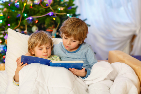 Two little blond sibling boys reading a book together in bed near Christmas tree with lights and illumination. Happy family, two children and friends. Standard-Bild