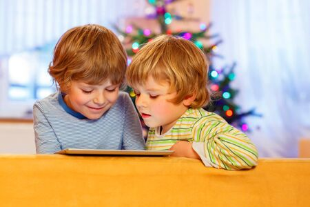 infant school: Two adorable little kid boys playing with tablet pc, indoors. Happy siblings toddlers, blond twins, looking at gift. With Christmas tree and lights on background.